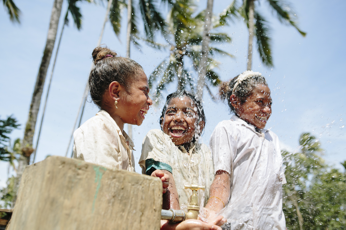 Children at tap with WaterAid Belu