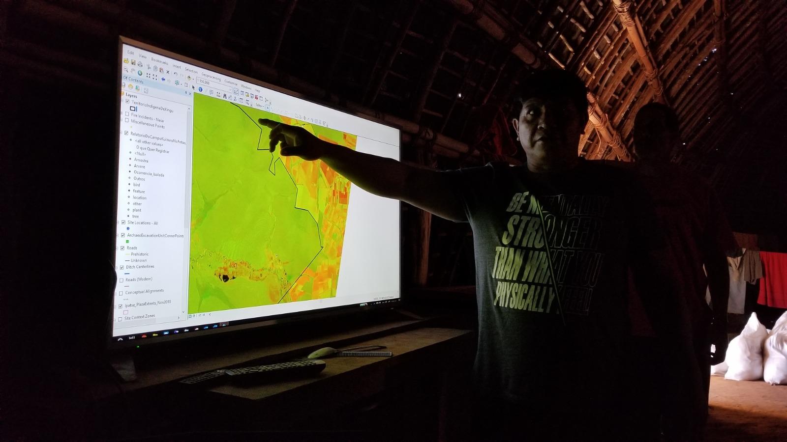 Yanama Kuikuro showing a satellite image of the Xingu territory