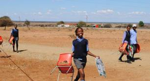 School girl takes a chair and tutudesk to school