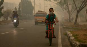 A boy cycles in Indonesia in smog