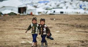 Syrian boys, whose family fled their home in Idlib, walk to their tent, at a camp for displaced Syrians, in the village of Atmeh, Syria, Monday, Dec. 10, 2012.jpg