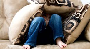 Child hiding under cushions