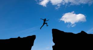 Man jumping across chasm to other side